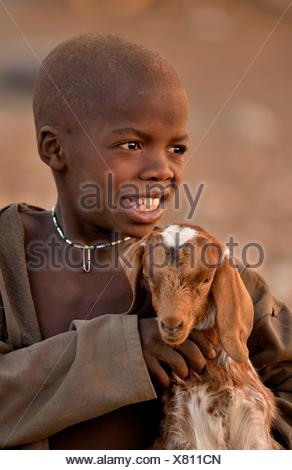 Himba boy with a goat, Ombombo, Kaokoland, Kunene, Namibia - Stock Photo