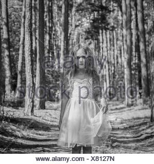 Portrait of sad girl (4-5) in forest - Stock Photo