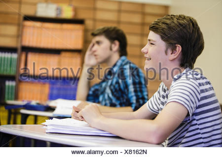 Male teenage high school students listening at desk in lesson - Stock Photo
