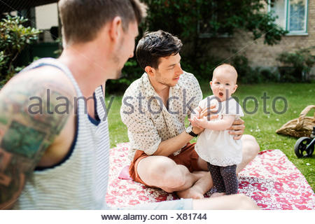 Gay couple looking at baby girl while sitting in yard