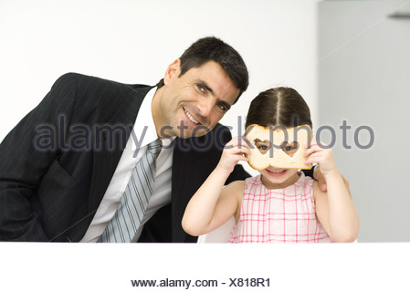Father and daughter sitting side by side, girl looking through slice of bread with heart-shaped holes, both smiling at camera - Stock Photo