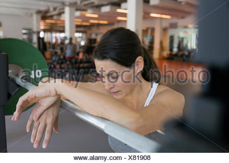 Woman resting and leaning on barbell at gym - Stock Photo