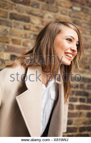 Woman with wide smile, brick wall in background - Stock Photo