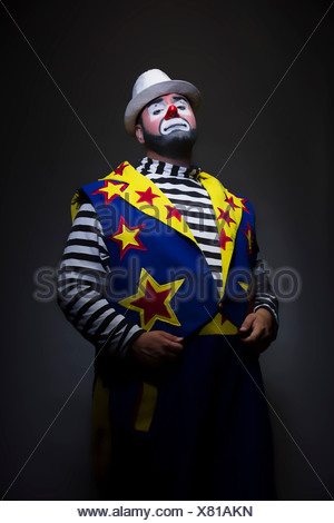 Studio portrait of clown with hands in pockets - Stock Photo