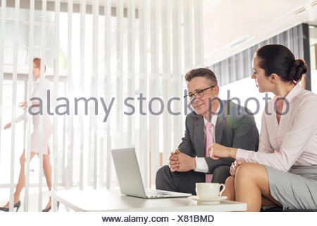 Businessman and businesswoman discussing in office - Stock Photo