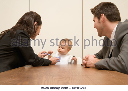 Parents feeding baby in board room - Stock Photo
