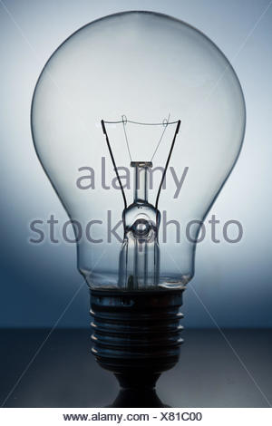 Close up of big light bulb standing on reflective surface - Stock Photo