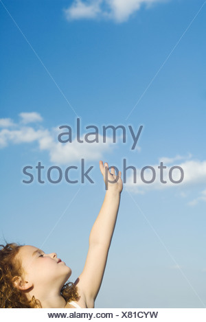 Little girl reaching one hand toward sky, head back, eyes closed, cropped view - Stock Photo