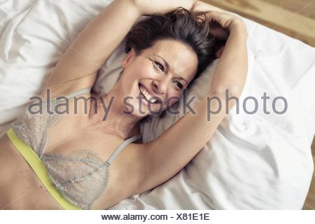 Overhead view of mature woman wearing bra lying on bed - Stock Photo