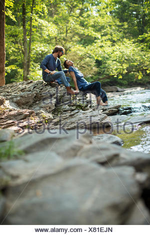 Two men seated in shade on the rocks by the river. - Stock Photo
