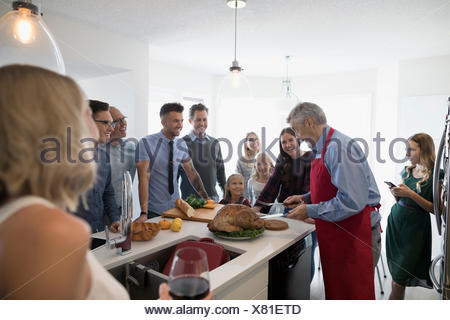 Multi-generation family preparing, carving Christmas turkey in kitchen - Stock Photo