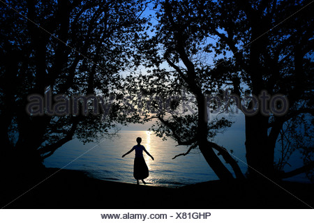 Silhouette of young woman standing by lake - Stock Photo