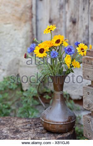 Fresh flowers in metal jug, outdoors - Stock Photo