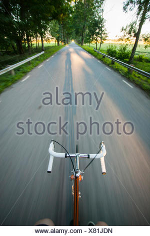 Sweden, Vastergotland, Lerum, Personal perspective of man on bicycle - Stock Photo