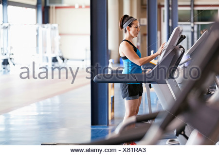 Woman exercising on treadmill in fitness center - Stock Photo