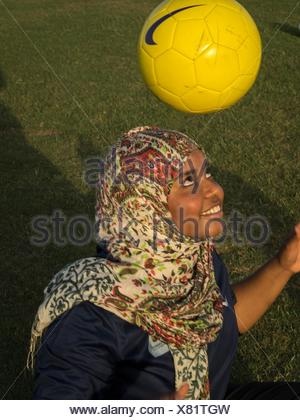 A girl, an assistant soccer coach, during a FutbolNet session at the Sultan School in Al Seeb. - Stock Photo