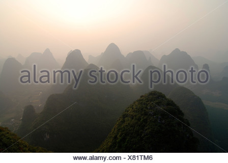 View from a hot-air balloon over the rocky karst landscape near Yangshuo in the evening haze, Guilin, Guangxi, China, Asia - Stock Photo