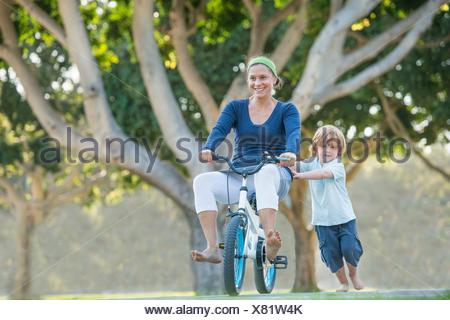 Mother sitting on son's bike, son pushing her along - Stock Photo