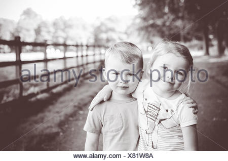 Boy and girl standing on footpath in park hugging - Stock Photo