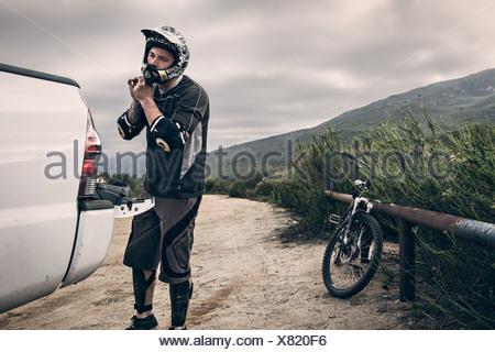 Downhill mountain biker putting on helmet