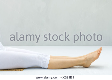 Woman with legs outstretched, barefoot, low section - Stock Photo
