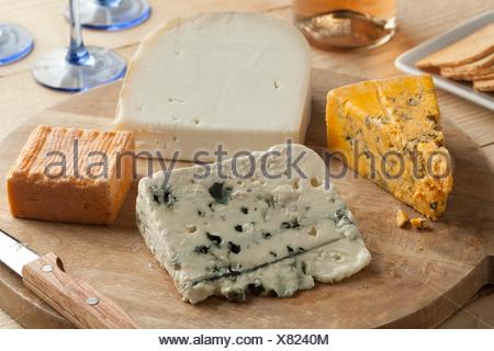 Variety of cheese on a wooden board for dessert. - Stock Photo