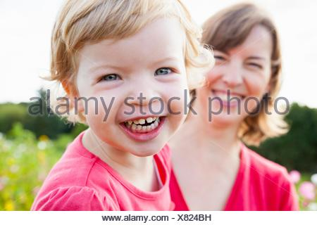 Close up portrait of mid adult mother and toddler daughter in flower field - Stock Photo