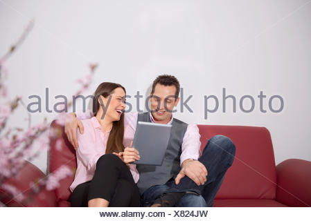 Young couple sitting sofa laughing tablet computer - Stock Photo