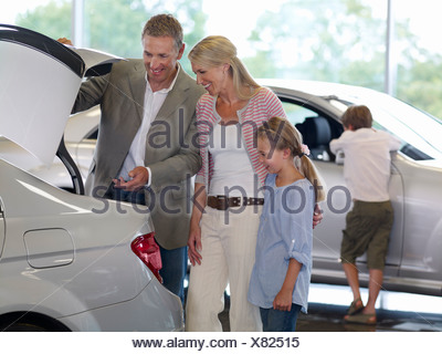 Family looking new car in showroom - Stock Photo