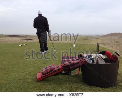 Rear view of a man playing golf, Scotland, UK - Stock Photo