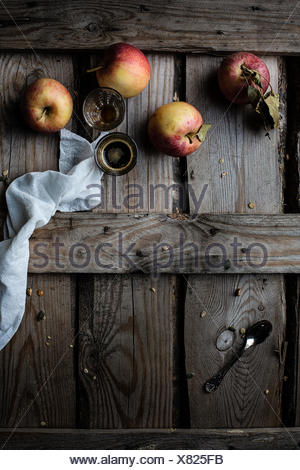 Apples and coffee on rustic wooden table - Stock Photo