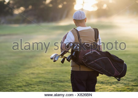 Rear view of man carrying golf bag - Stock Photo