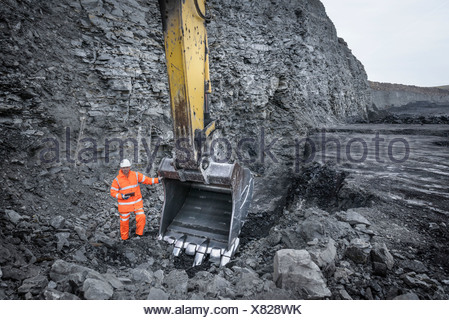 Coal miner inspects excavation in surface coal mine - Stock Photo