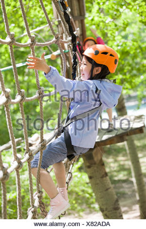 Happy Chinese children playing in tree top adventure park - Stock Photo