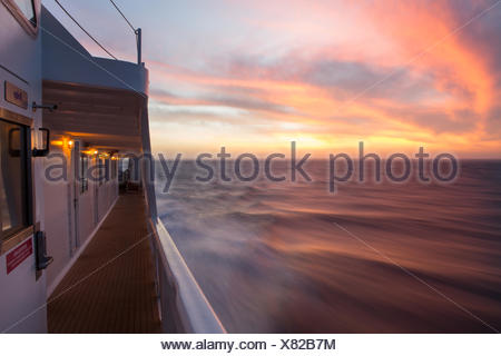 The rising sun illuminates clouds above the waters near Isla Coiba National Park as an expedition cruise ship,the National Geographic Sea Lion,speeds through the water. - Stock Photo