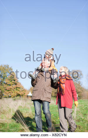 Grandparents walking outdoors with grandson - Stock Photo