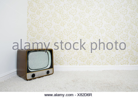 Retro television in corner of room with patterned wallpaper - Stock Photo