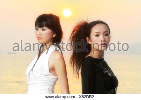 two young asians in front of sunset - Stock Photo