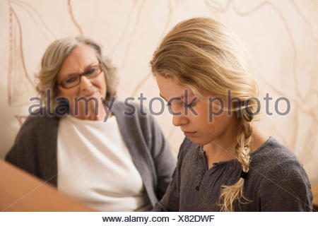 Girl playing the piano watched by grandmother - Stock Photo