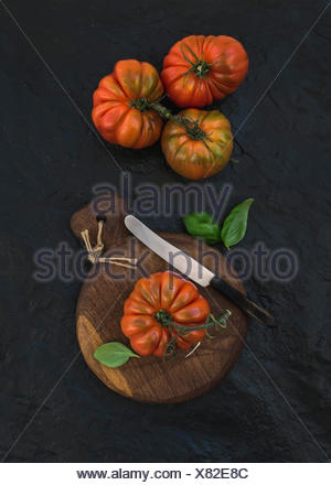 Fresh ripe hairloom tomatoes and basil leaves on rustic wooden board over black stone background, top view - Stock Photo