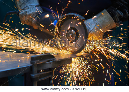 Cutting a steel plate with an angle grinder - Stock Photo
