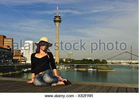 Girl sits at Dusseldorf Mediahafen - Stock Photo