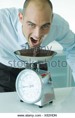 Man leaning toward stack of chocolate chunks on kitchen scale with mouth wide open - Stock Photo