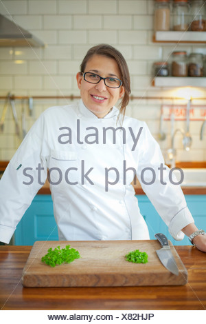 Portrait of female chef in commercial kitchen - Stock Photo
