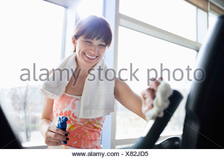 Woman cleaning stationary bike in fitness center - Stock Photo