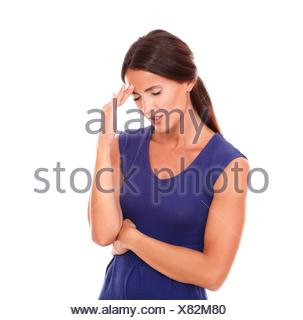 Young latin lady suffering from headache with closed eyes and looking ill in white background. - Stock Photo