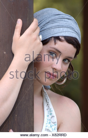 portrait of a beautiful woman with headress, holding on at a post, Germany - Stock Photo