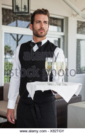 Handsome waiter holding tray of champagne - Stock Photo