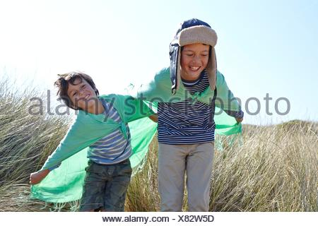 Two young boys, wearing fancy dress, playing on beach - Stock Photo