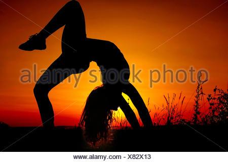 Girl (11-12) doing gymnastics - Stock Photo